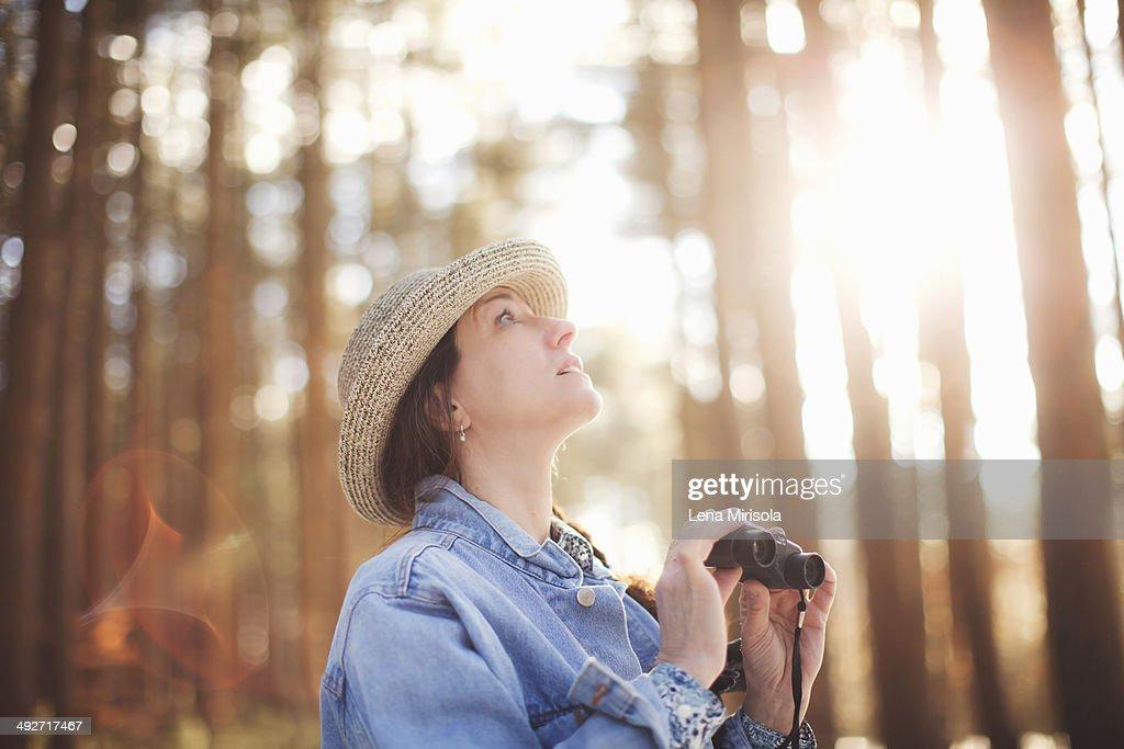 Mature female bird watcher in forest