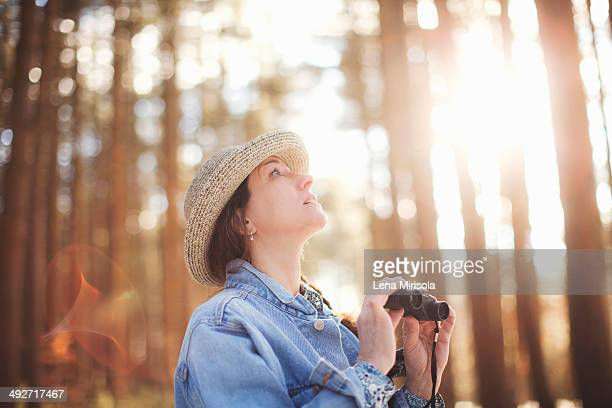 Mature female bird watcher in forest