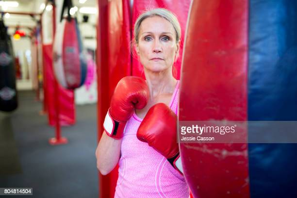 Mature female boxer stands next to punch bag in gym with boxing gloves on