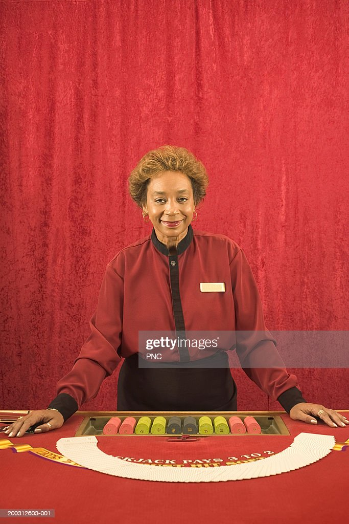 Mature female card dealer standing beside game table, portrait