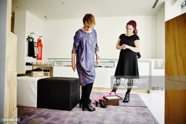 Mature female customer trying on shoes in boutique