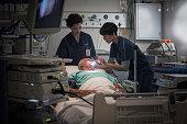 Mature female doctor and female nurse examining patients throat