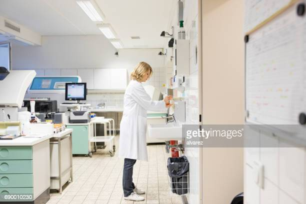 Mature female doctor dispensing soap by sink