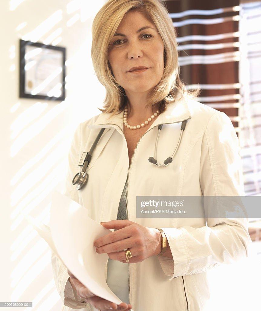 Mature female doctor holding medical chart, portrait : Stock Photo