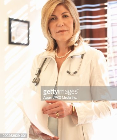 Mature female doctor holding medical chart, portrait : Stock Photo
