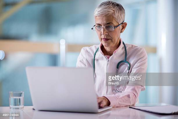 Mature female doctor working on laptop in the office.