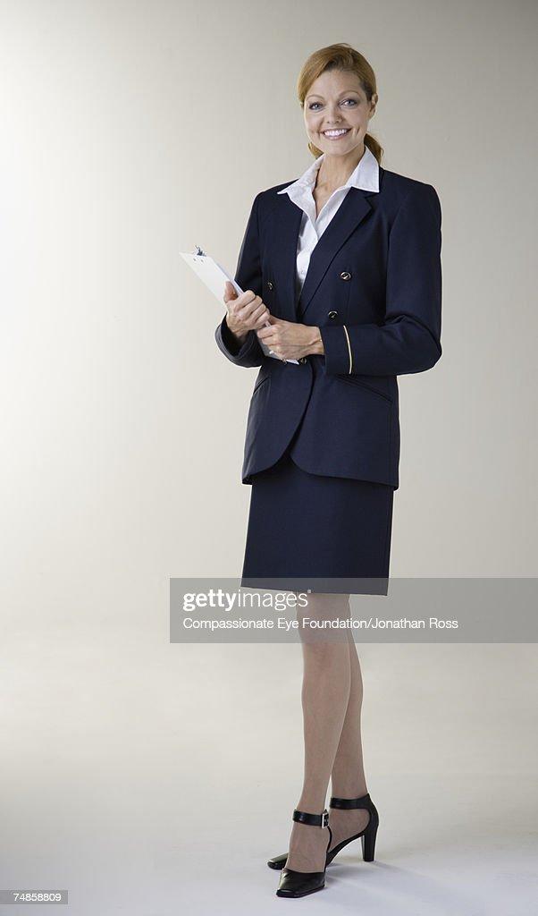 Mature female flight attendant holding clipboard, smiling, portrait : Stock Photo