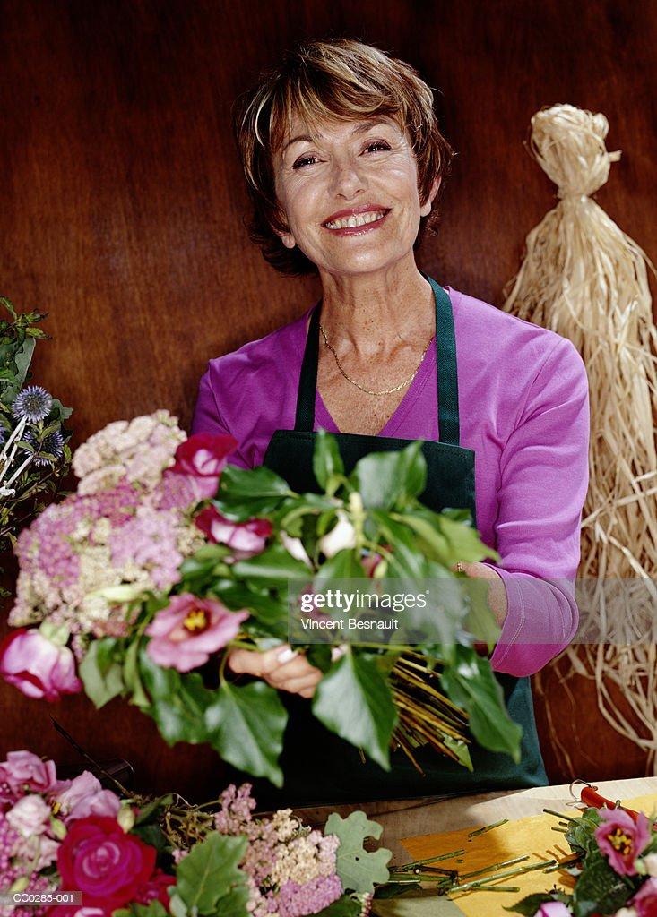 Mature female florist preparing a bouquet, portrait, close-up : Stock Photo