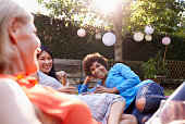 Mature Female Friends Enjoying Drinks In Backyard Together