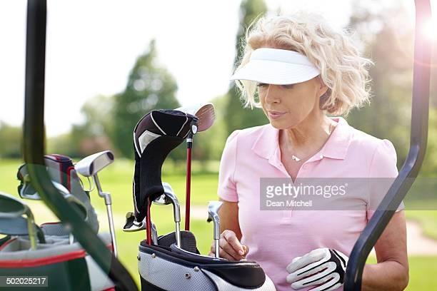 Mature female golfer choosing a right club