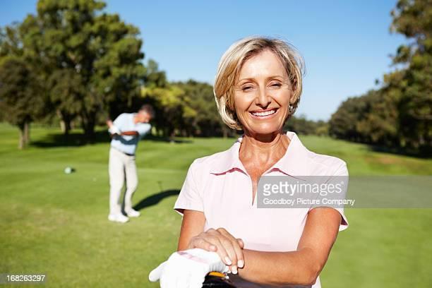 Golfeur souriant, femme d'âge mûr