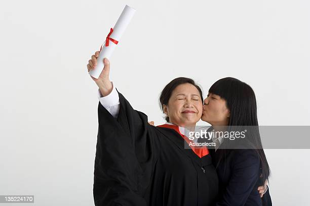 Mature female graduate holding a diploma and her daughter kissing on her cheek