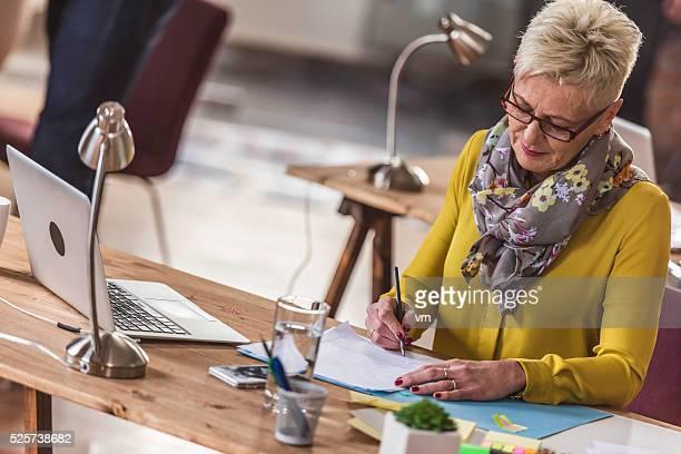 Mature female graphic designer making sketches