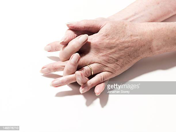 Mature female hands together on table