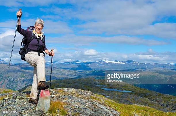 Mature female hiker with backpack, overlooking mountain landscape