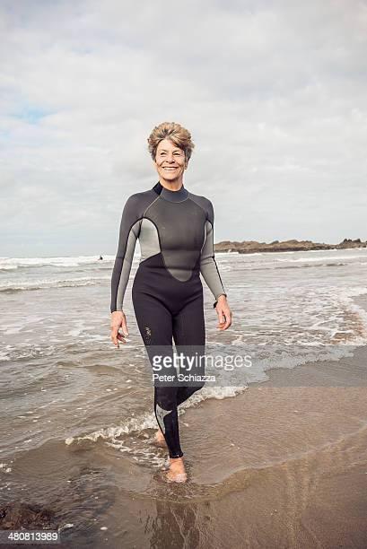 Mature female paddling on Devon coast, UK