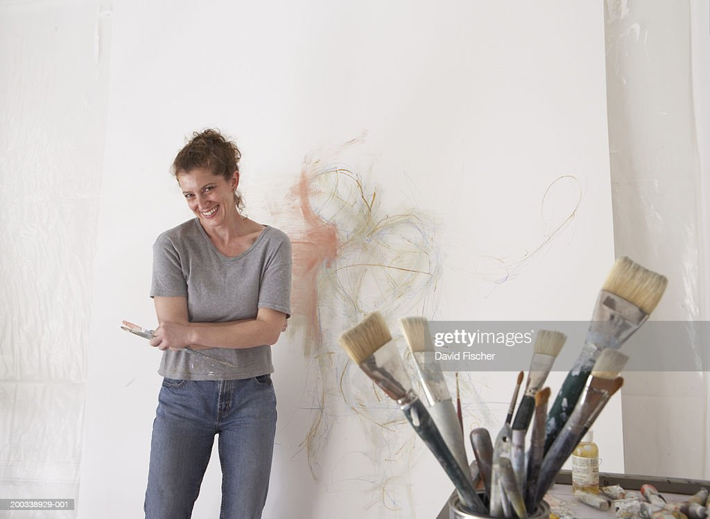 Mature female painter smiling next to canvas and brushes, portrait
