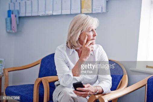 Mature female patient with mobile phone in hospital waiting room
