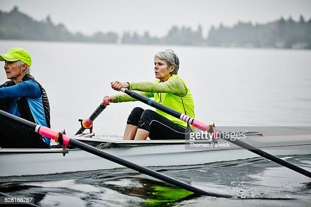 Mature female rowers practicing on rainy morning