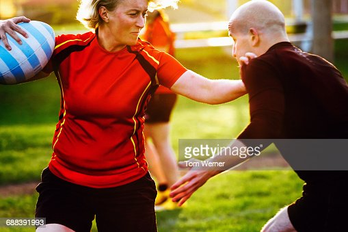 Mature female rugby player with trainer