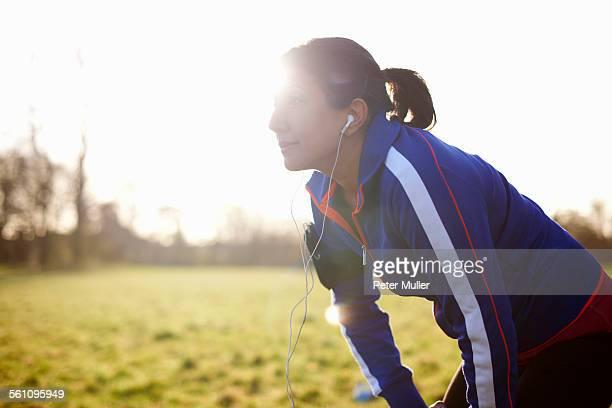 Mature female runner in field taking a break