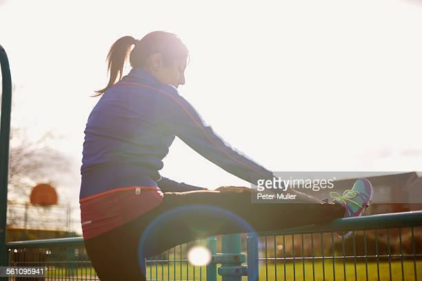 Mature female runner stretching leg on park fence