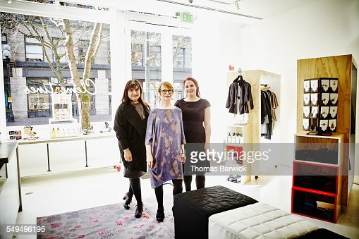 Mature female store owner standing with employees
