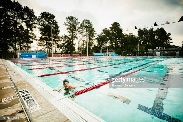 Mature female swimmer finishing set during early morning workout in outdoor pool