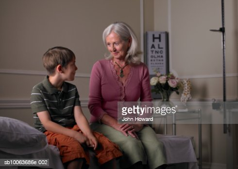 Mature female therapist sitting with boy (9-11) in practice room : Stock Photo