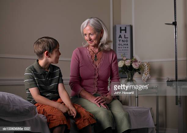 Mature female therapist sitting with boy (9-11) in practice room