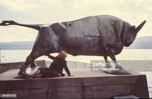 A mature female tourist jokingly pretends to grab the crotch area of a large metal statue of a bull 1975