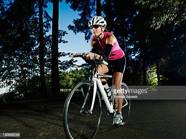 Mature female triathlete riding bicycle on path