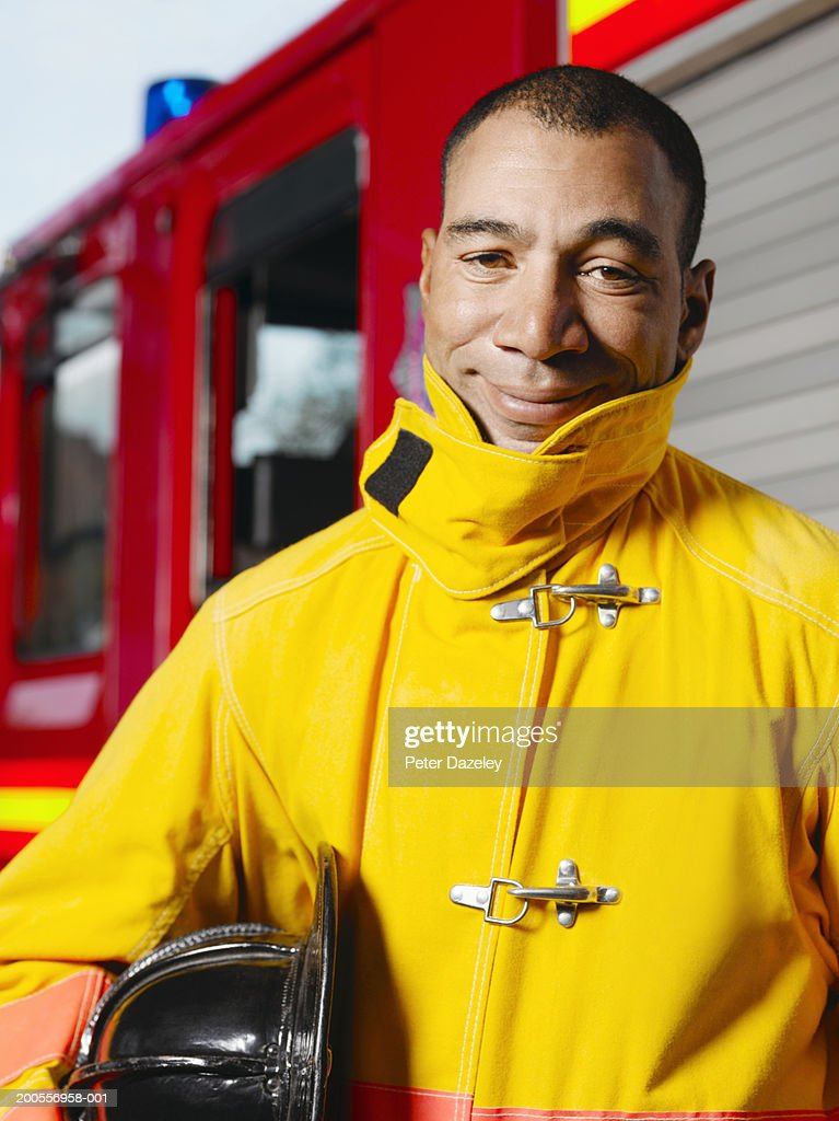 Mature fireman standing by fire engine, smiling, portrait : Stock Photo