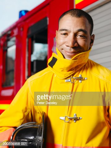 Mature fireman standing by fire engine, smiling, portrait : Photo