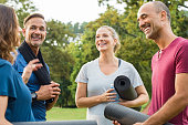 Happy multiethnic group of mature people holding yoga mat and towel in conversation after exercising at park. Happy senior men and smiling women talking to each other after an exercising class outdoor