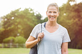 Senior beautiful woman holding a grey yoga mat preparing for exercise. Portrait of a mature smiling woman with fitness mat in the park.