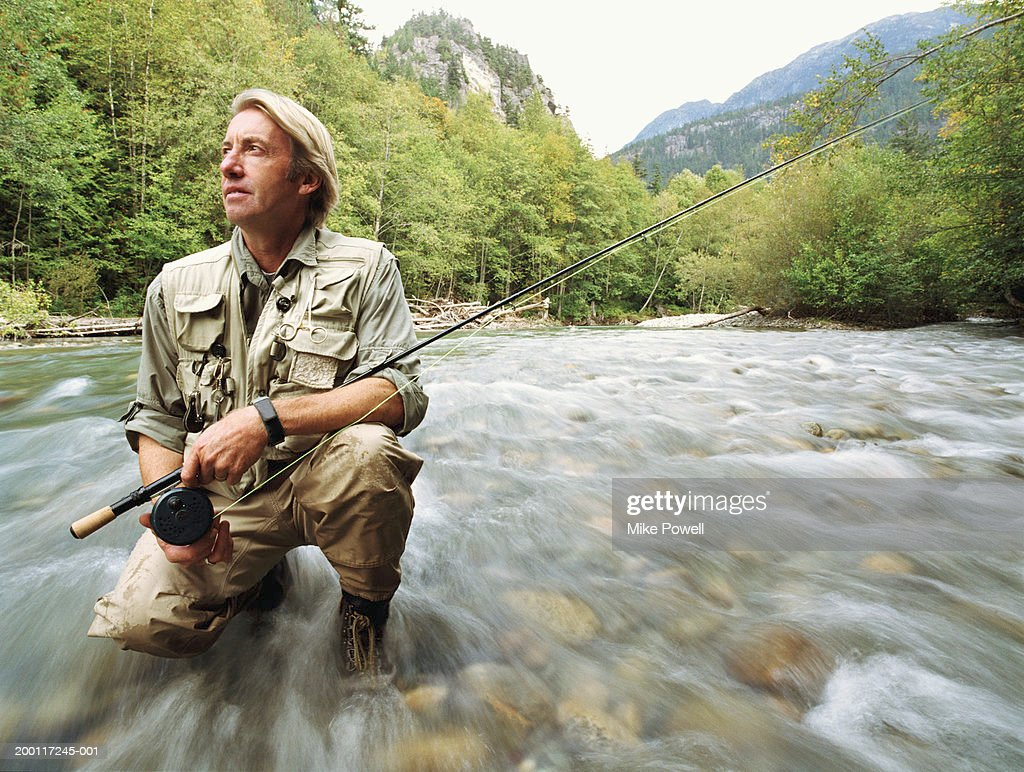 Mature fly fisherman holding rod, kneeling in river, blurred motion : Stock Photo