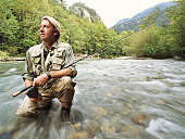 Mature fly fisherman holding rod, kneeling in river, blurred motion