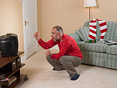 Mature football supporter watching television and raising fists with look of disbelief