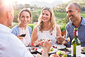 Group of mature people eating together in a vineyard in a summer day. Happy woman sipping wine while talking to friends during a lunch in a winery. Happy senior couple having dinner with wine at sunse