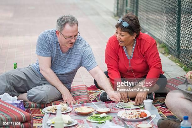 Amigos maduros, desfrutar o almoço piquenique Emirati Árabe fora, Dubai, EAU
