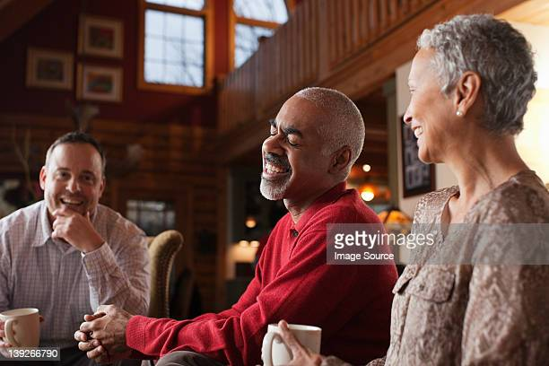 Mature friends laughing together in living room