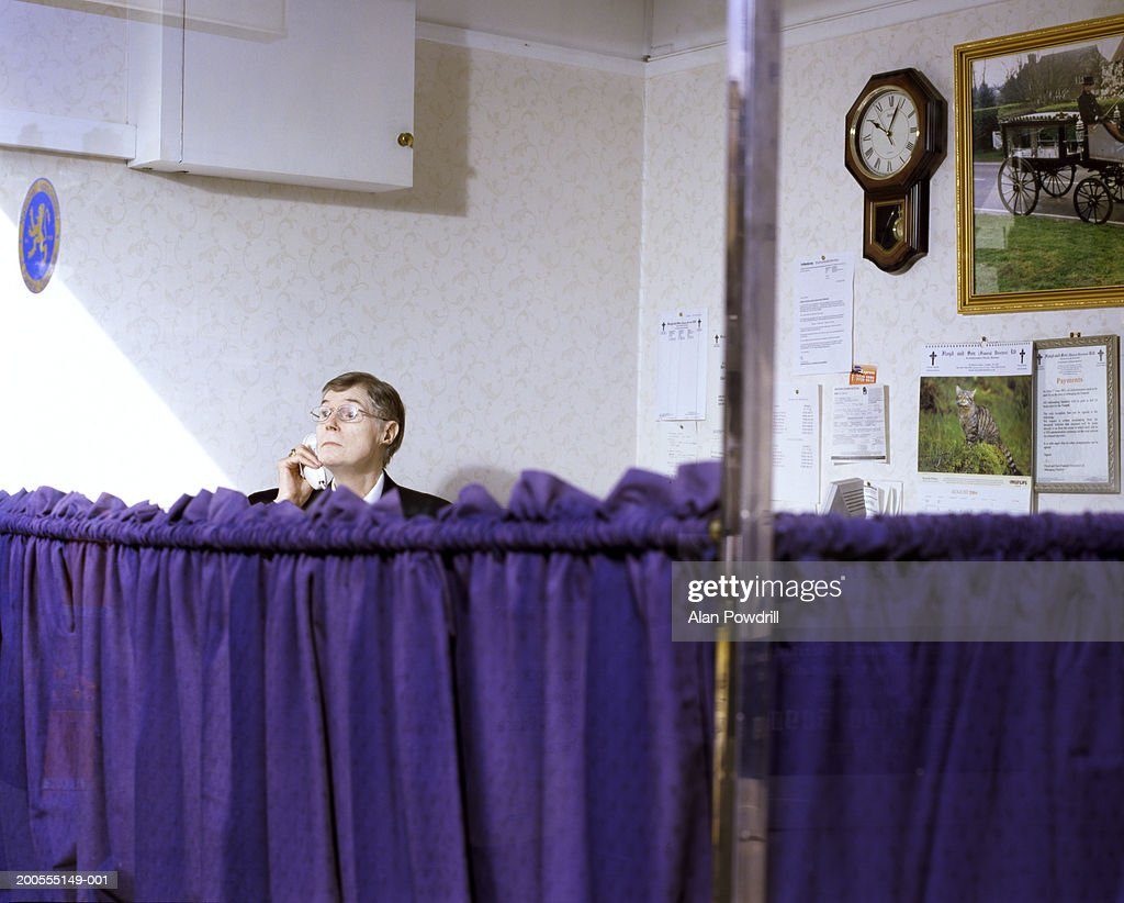 Mature funeral director using phone in office : Stock Photo