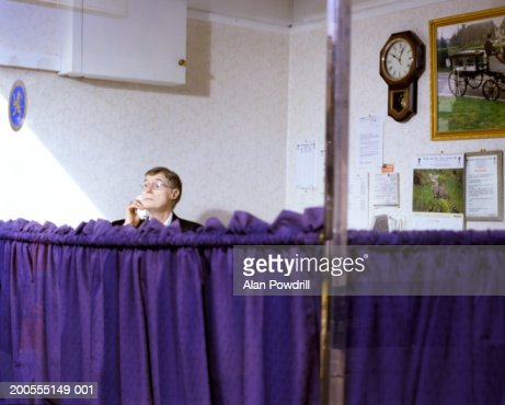 Mature funeral director using phone in office : Foto stock
