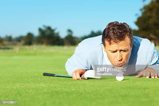Mature golfer blowing at the ball