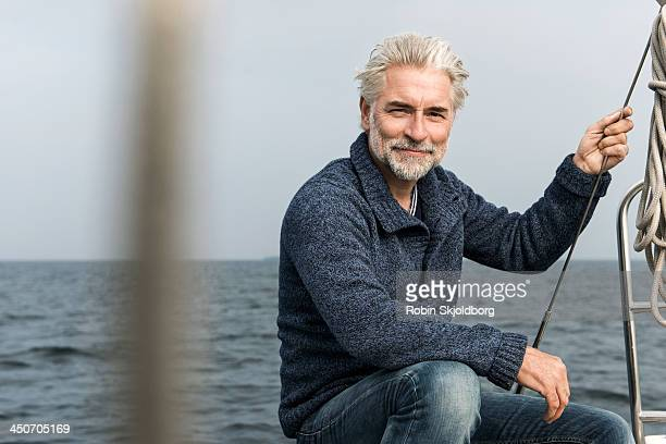 Mature grey haired man on board a sailing boat