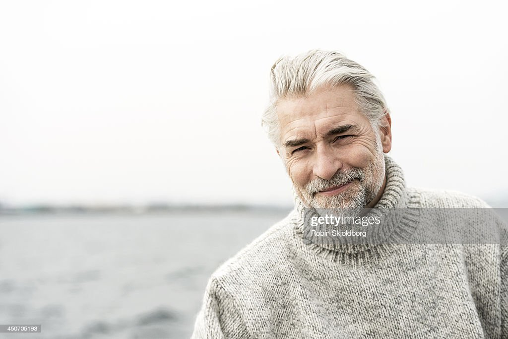 Mature grey haired man wearing a sweater : Stock Photo