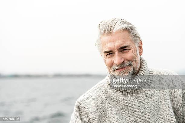 Mature grey haired man wearing a sweater