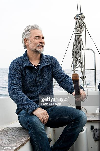 Mature greyhaired man in sailing boat