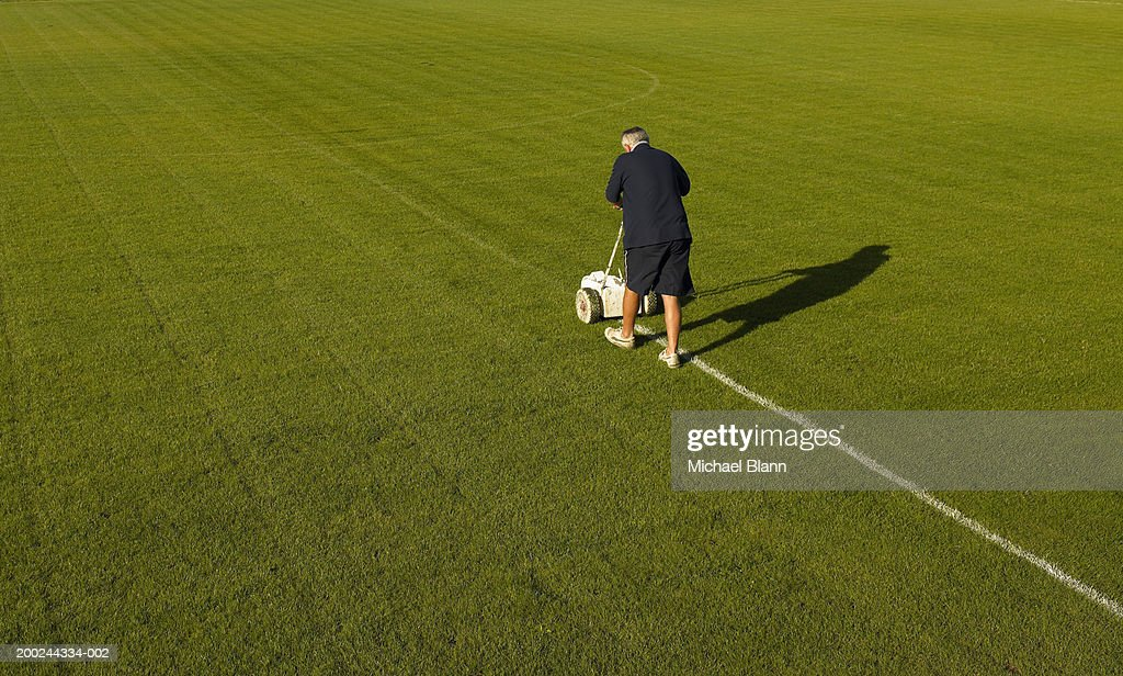 Mature groundsman marking lines on football pitch, rear view : Stock Photo